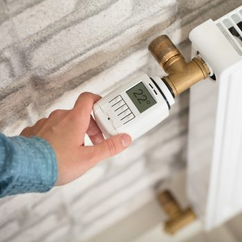 A Person's Hand Adjusting Temperature On Thermostat Of Radiator
